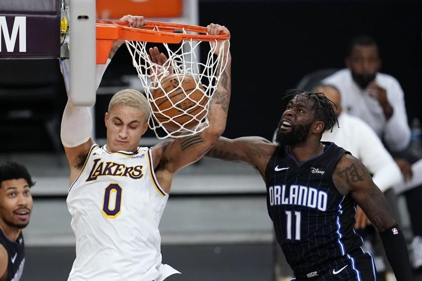 Los Angeles Lakers forward Kyle Kuzma (0) dunks past Orlando Magic forward James Ennis III (11) during the second half of an NBA basketball game Sunday, March 28, 2021, in Los Angeles. (AP Photo/Marcio Jose Sanchez)