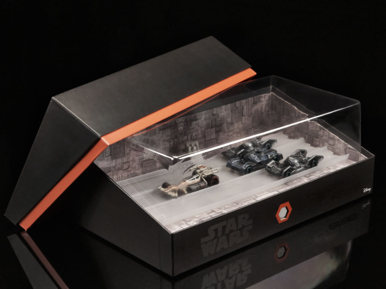 "<p>The top of the cardboard case can be removed to display the four die-cast ""carships,"" with the trench re-conceived as race track.</p>"
