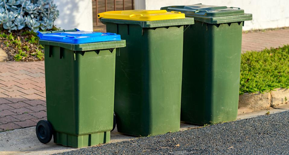 three council rubbish bins waiting to be picked up