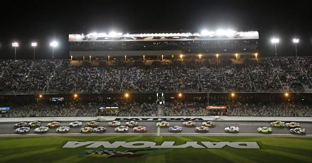 Martin Truex Jr., top left, and Carl Edwards, bottom left, lead the group of cars to start the second of two NASCAR Sprint Cup qualifying auto races at Daytona International Speedway in Daytona Beach, Fla., Thursday, Feb. 20, 2014. (AP Photo/John Raoux)