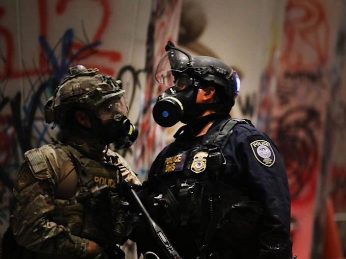 Federal police guard the Mark O. Hatfield federal courthouse in downtown Portland as the city experiences another night of unrest on July 24, 2020 in Portland, Oregon.