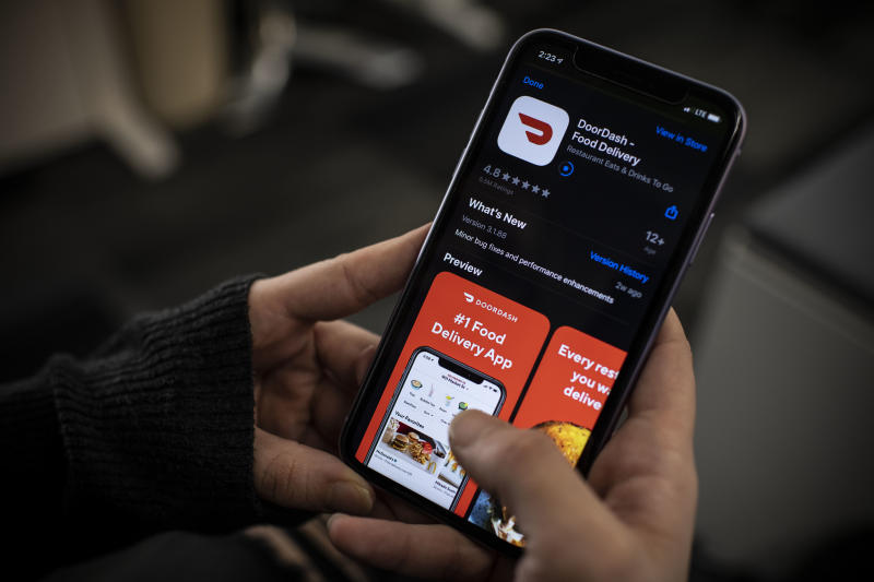 An AFP journalist checks the DoorDash food delivery application on her smartphone on February 27, 2020 in Washington, DC. - DoorDash on February 27, 2020 began the process of going public with a US stock offering that could value the popular restaurant meal delivery service at more than $10 billion. San Francisco-based DoorDash said it confidentially registered with market regulators at the Securities and Exchange Commission for an initial public offering of shares. The price and number of shares had yet to be determined. DoorDash backers including Japanese financial titan Softbank have pumped more than $2 billion into the startup, which last year was given a valuation of nearly $13 billion. (Photo by Eric BARADAT / AFP) (Photo by ERIC BARADAT/AFP via Getty Images)