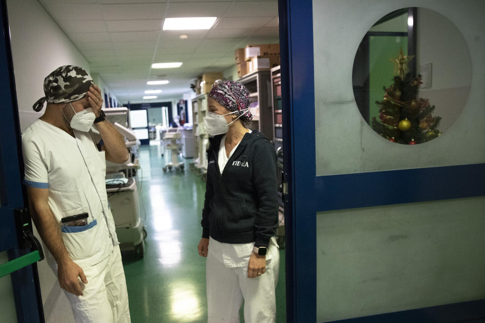 Nurses Glenda Grossi, right, talks with her husband Maurizio di Giacobbe at the end of her shift in the COVID-19 ICU of the Tor Vergata Polyclinic Hospital, Sunday, Dec. 13, 2020. The coronavirus pandemic has posed unprecedented challenges for families around the world managing work and home life with children kept home from school and after-school activities. For the Di Giacobbe family, the juggling is even more complicated since mom and dad are intensive care nurses in the same COVID-19 ward and spend their days tag-teaming shifts, trying to give their patients the level of personal care and attention they would give their own children. (AP Photo/Alessandra Tarantino)