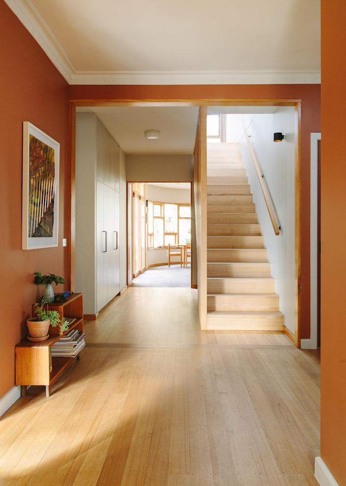 AFTER: The lovely, wide entryway is painted in a paprika shade from Dulux, and complements the Australian hardwood staircase.