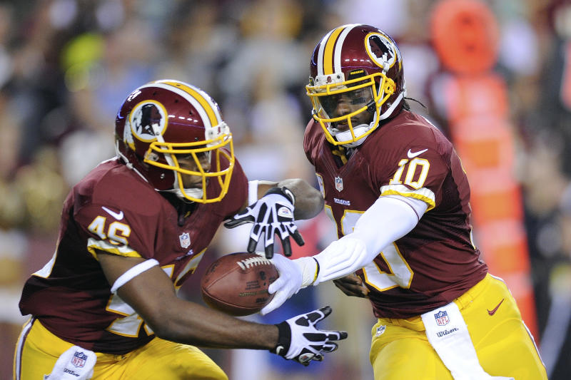 Washington Redskins quarterback Robert Griffin III hands off to running back Alfred Morris, left, during the first half of an NFL football game against the Philadelphia Eagles in Landover, Md., Monday, Sept. 9, 2013. (AP Photo/Nick Wass)