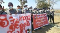 Police officers holding banners join the protest against the military coup in Kayah State