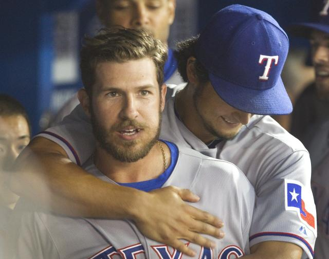 Texas Rangers' J. P Arencibia gets a hug from starting pitcher Yu Darvish after he hit a three-run home run off Toronto Blue Jays starting pitcher R.A. Dickey during the seventh inning of a baseball game Friday, July 18, 2014, in Toronto. (AP Photo/The Canadian Press, Fred Thornhill)