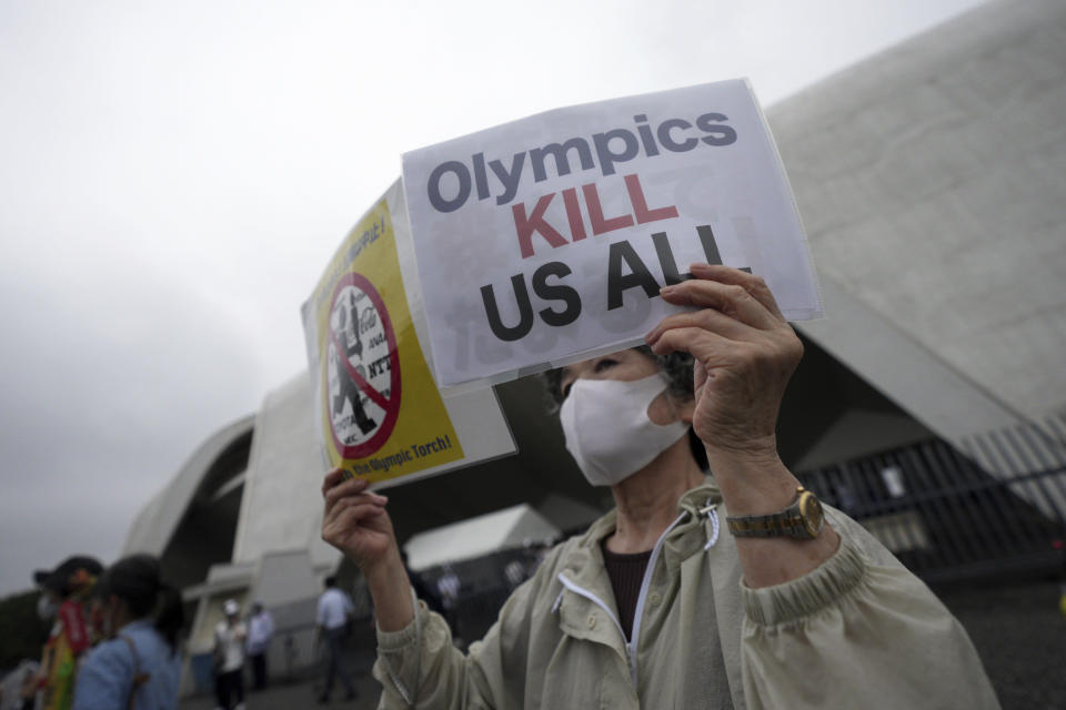 One of people against Olympic Games protests near Komazawa Olympic Park, where the unveiling ceremony for Olympic Flame of the Tokyo 2020 Olympic torch relay is held Friday, July 9, 2021, in Tokyo. (AP Photo/Eugene Hoshiko)