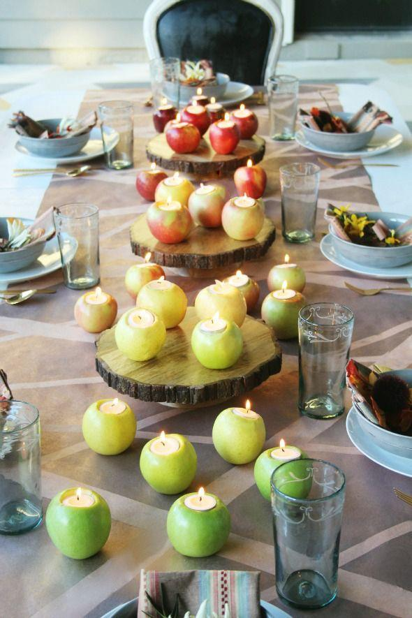 """<p>You don't have to go over-the-top to create a stunning scene. Rather than opt for a <a href=""""https://www.countryliving.com/diy-crafts/g2009/fall-centerpieces/"""" rel=""""nofollow noopener"""" target=""""_blank"""" data-ylk=""""slk:big, dramatic centerpiece"""" class=""""link rapid-noclick-resp"""">big, dramatic centerpiece</a>, interior designer Jenny Komenda used an apple-themed ombre effect to create something much more visually stimulating. </p><p>Hurricane lanterns are another great option for outdoor dinners. They add light for function, glow for ambiance, and their shape and size make them practical in windy settings.</p>"""