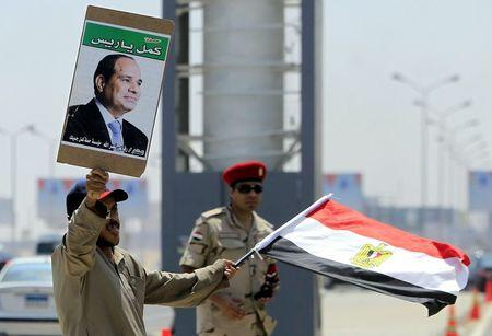 File photo shows a man carrying a portrait of Egyptian President Sisi and an Egyptian flag standing next to a soldier during the funeral of Egyptian public prosecutor Hisham Barakat, on the second anniversary of the June 30 protests in Cairo