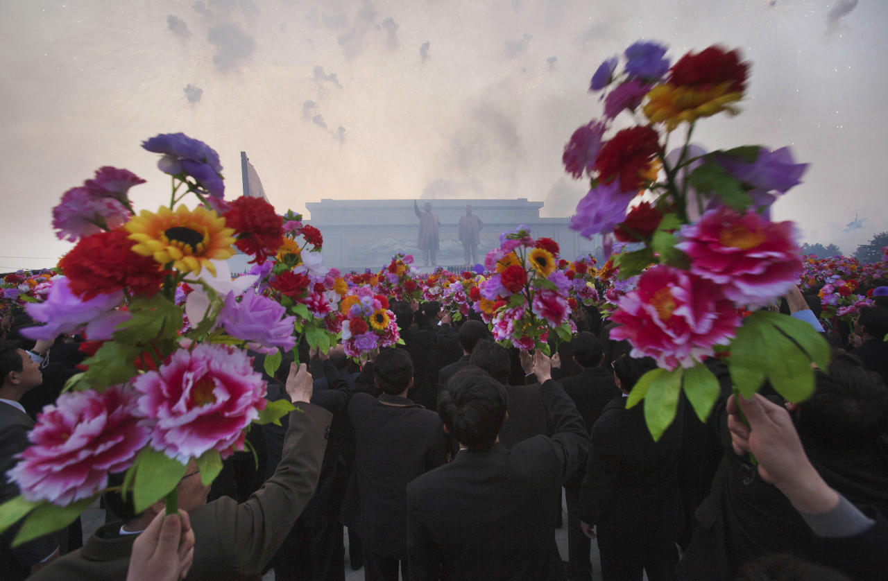 FILE - North Koreans wave artificial flowers at an unveiling ceremony for statues of the late leaders Kim Il Sung and Kim Jong Il in Pyongyang, North Korea, on April 13, 2012. (AP Photo/David Guttenfelder, File)