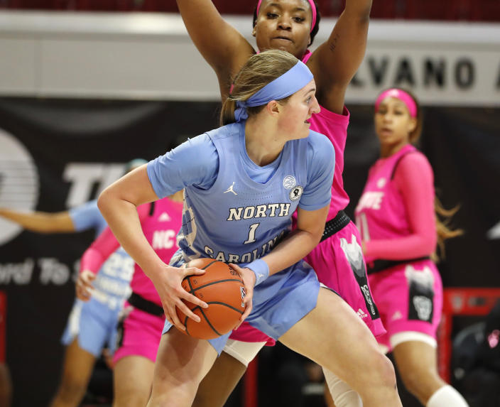 North Carolina's Alyssa Ustby (1) looks to get out of the pressure applied by N.C. State's Kayla Jones (25) during the first half of a college basketball game in the annual Play4Kay game at Reynolds Coliseum in Raleigh, N.C., Sunday, Feb. 21, 2021. (Ethan Hyman/The News & Observer via AP)