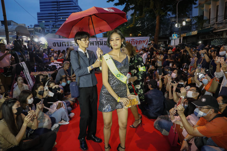 "Protesters perform on a mock fashion ""red carpet"" while taking part in a protest in Bangkok, Thailand, Thursday, Oct. 29, 2020. The protesters continue to gather Thursday, led by their three main demands of Prime Minister Prayuth Chan-ocha's resignation, changes to a constitution that was drafted under military rule and reforms to the constitutional monarchy. (AP Photo/Gemunu Amarasinghe)"