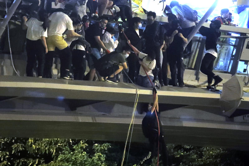 Protestors use a rope to lower themselves from a pedestrian bridge to waiting motorbikes in order to escape from Hong Kong Polytechnic University and the police in Hong Kong, Nov. 18, 2019. (Photo: Kin Cheung/AP)