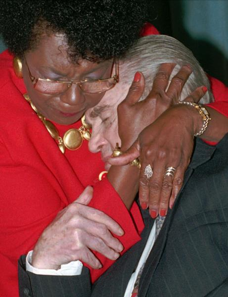 FILE - This is an Aug. 26, 1994 file photo of former four-term Alabama Gov. George C. Wallace in an emotional moment as he hugs friend Connie Harper at a celebration of Wallace's 75th birthday. Fifty years ago, Wallace stood in a doorway at the University of Alabama and tried to block two black students from enrolling. Wallace backed down when President John Kennedy federalized the Alabama National Guard and ordered troops to Tuscaloosa. Wallace's daughter, Peggy Wallace Kennedy, said her family has lived in the shadow of the schoolhouse door ever since. (AP Photo/Dave Martin, File)