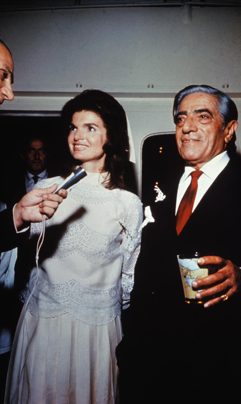 (Original Caption) Aristotle Onassis married Jackie Kennedy on his private island. Onassis is shown with a drink in his hand and Jackie is smiling and talking into a microphone and wearing her white wedding dress.