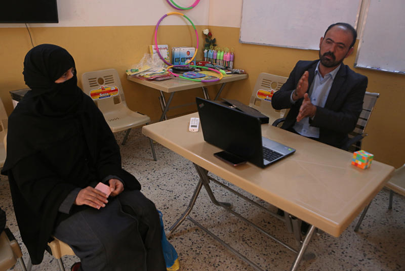 In this Feb. 26, 2019 photo, a widow of Islamic State group militant, Muthanna Hussein, listens to legal advice, at a clinic supported by the Norwegian Refugee Council, in west Mosul, Iraq. Thousands of Iraqi families face crushing social and legal discrimination -- all because of the choices their male relatives made under the Islamic State group's rule. They've been disowned by relatives and abandoned by the state. Registrars refuse to register their births, marriages or divorces; schools won't let their children enroll. (AP Photo/Khalid Mohammed)