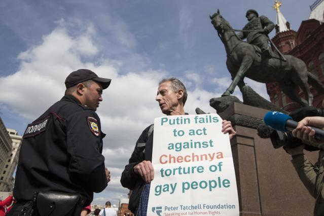 "A Russian police officer speaks to Gay rights activist Peter Tatchell as he holds a banner that read ""Putin fails to act against Chechnya torture of gay people"" in front of the the monument of Soviet Marshal Georgy Zhukov, near Red Square in Moscow, Russia, Thursday, June 14, 2018. A British LGBT activist has been detained has been detained near the Red Square for holding a one-man protest against Russia's abuse of gays. (AP Photo/Alexander Zemlianichenko)"