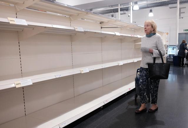 A woman looks at empty shelves in a Sainsbury's store in London, as coronavirus continues to affect the UK with the UK death toll reaching 71 people.