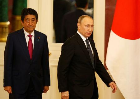 Russian President Vladimir Putin (R) and Japanese Prime Minister Shinzo Abe enter a hall during a media briefing following their meeting at the Kremlin in Moscow, Russia, April 27, 2017. REUTERS/Sergei Karpukhin/Files