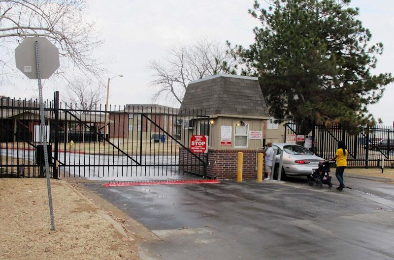 A car approaches the guard shack at the entrance to the Fairmont Terrace apartment complex on Thursday, Feb. 7, 2013, in Tulsa, Okla. After four women were found shot to death at the run-down complex last month, apartment managers have beefed up security at the entrance to the complex. (AP Photo/Justin Juozapavicius)
