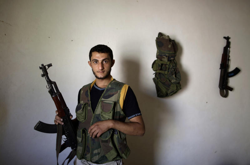 In this Tuesday, Sept. 4, 2012, photo, Syrian rebel fighter, Ahmad Hussein, 22, a former factory worker, poses for a picture at a house where he and others wait their turn to go and fight against government forces in Aleppo, in Marea on the outskirts of Aleppo city, Syria. Syria's rebels have turned to a new tactic of attacking bases, trying to stop the jets and attack helicopters that have wreaked devastation on their fighters and civilians in the battleground city of Aleppo and the nearby countryside.(AP Photo/Muhammed Muheisen)