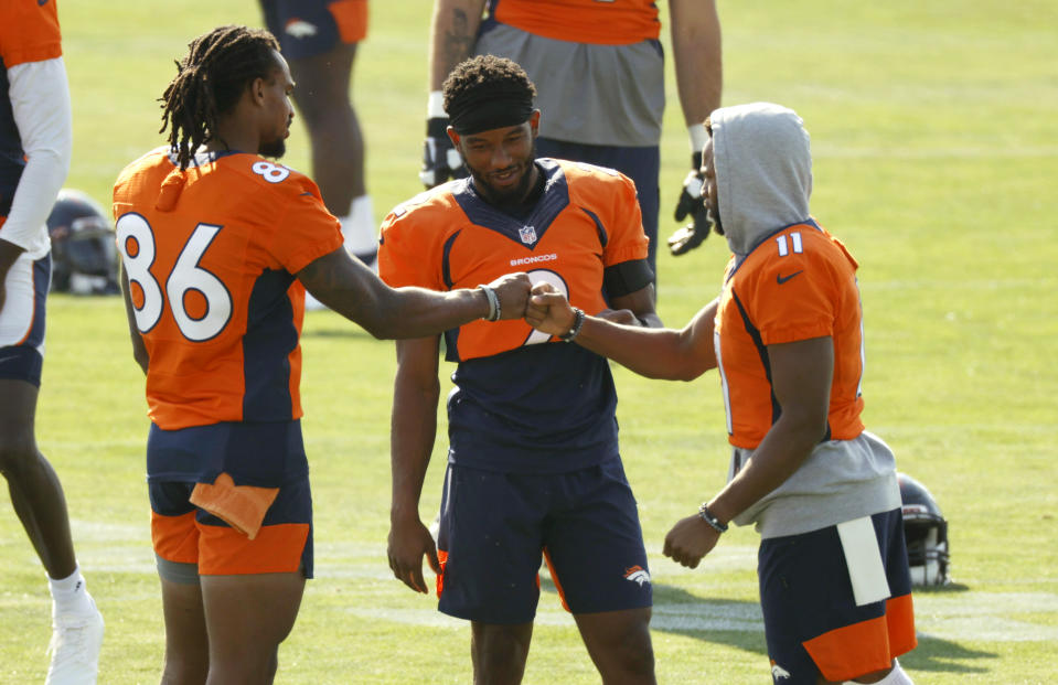 From left, Denver Broncos wide receivers Tyrie Cleveland, Kendall Hinton and Diontae Spencer greet each other before taking part in drills at the team's NFL football training camp Friday, Aug. 14, 2020, in Englewood, Colo. (AP Photo/David Zalubowski)