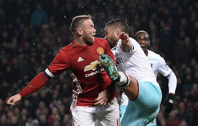 Manchester United's Wayne Rooney (L) reacts after clashing with the foot of West Ham United's Winston Reid at Old Trafford in Manchester, north west England, on November 30, 2016 (AFP Photo/Oli Scarff)