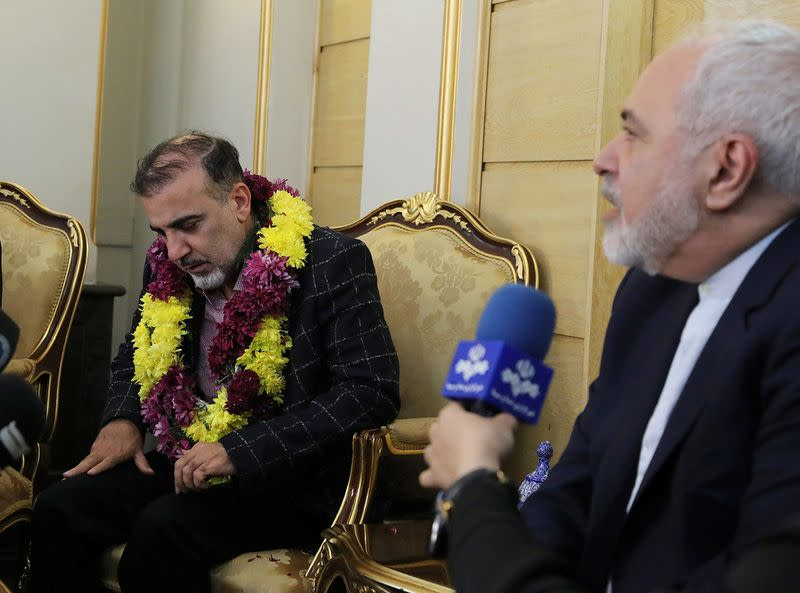 Iranian professor Massoud Soleimani sits next Iran's Foreign Minister Mohammad Javad Zarif during his arrival at Mehrabad airport, in Tehran