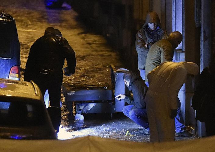 Policemen and forensic police work in a marked out perimeter in Colline street in Verviers, eastern Belgium, on January 15, 2015 (AFP Photo/John Thys)