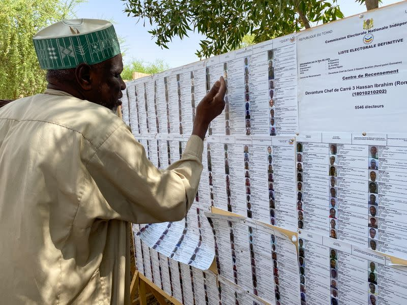 A man searches for his name on a registration list at a polling station during the presidential election in N'Djamena