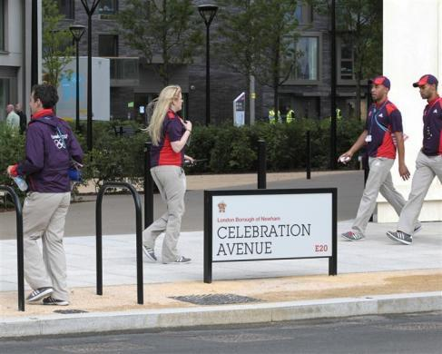 LOCOG employees cross Celebration Avenue in the Olympic Village built for the London 2012 Olympic Games in Stratford, east London on June 29, 2012.