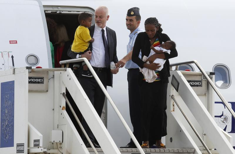 Mariam Yahya Ibrahim of Sudan holds one of children next to Lapo Pistelli, Italy's vice minister for foreign affairs, holding her other child, as they land at Ciampino airport in Rome
