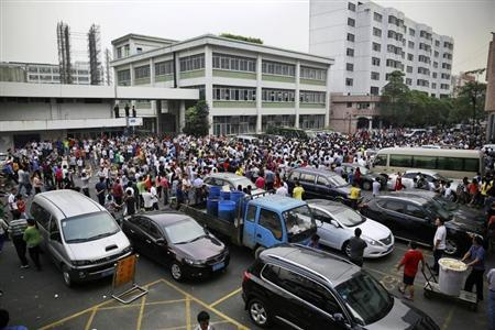 Workers protest during a strike as police stand guard at the factory area of Yue Yuen Industrial, in Dongguan