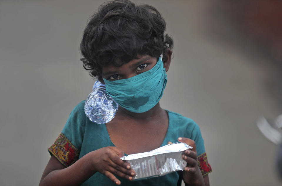 A girl wearing a face mask walks with a bottle of drinking water and a food packet that she received from a food distribution site in Mumbai, India, Saturday, June 20, 2020. India is the fourth hardest-hit country by the COVID-19 pandemic in the world after the U.S., Russia and Brazil. (AP Photo/Rafiq Maqbool)