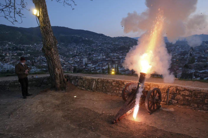 A man fires a vintage canon to signal the breaking of fast shortly after sunset in Sarajevo, Bosnia, April 24, 2020, during the first day of the holy fasting month of Ramadan. (AP Photo/Kemal Softic)