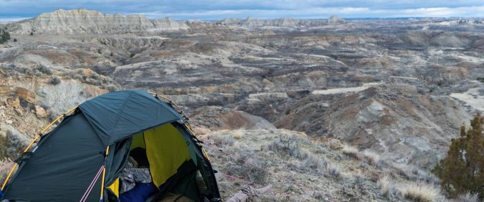 Campsite with a tent and hunting gear in the badlands area of the border of Eastern Montana and Western North Dakota on an early winter day. Overcast sky. Concept for public / BLM land use