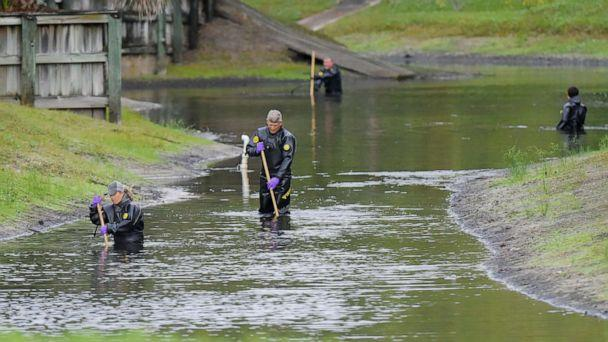 PHOTO: Law enforcement investigators in dry suits search the small retention pond near the entrance of the Southside Villas apartment complex in Jacksonville, Fla., Nov. 6, 2019. (Bob Self/The Florida Times-Union via AP)
