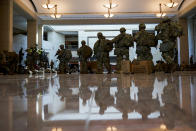 Troops move inside the Capitol Visitor's Center to reinforce security at the Capitol in Washington, Wednesday, Jan. 13, 2021. The House of Representatives is pursuing an article of impeachment against President Donald Trump for his role in inciting an angry mob to storm the Capitol last week. (AP Photo/Alex Brandon)