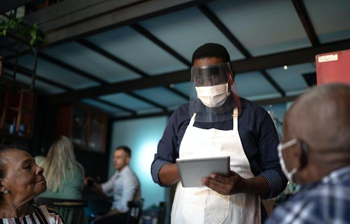 """<span class=""""caption"""">People who dine out after the CDC recently changed mask guidelines are counting on the honor system. </span> <span class=""""attribution""""><a class=""""link rapid-noclick-resp"""" href=""""https://www.gettyimages.com/detail/photo/waiter-taking-clients-order-using-a-digital-tablet-royalty-free-image/1255797795?adppopup=true"""" rel=""""nofollow noopener"""" target=""""_blank"""" data-ylk=""""slk:FG Trade/Getty Images"""">FG Trade/Getty Images</a></span>"""