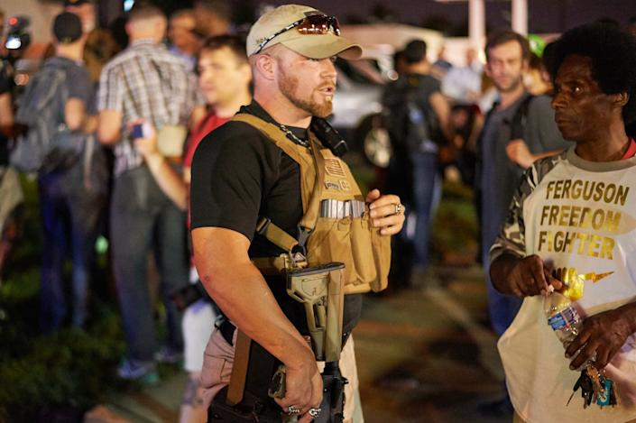 A member of the Oath Keepers walks with his personal weapon on the street during protests in 2015 in Ferguson, Mo.