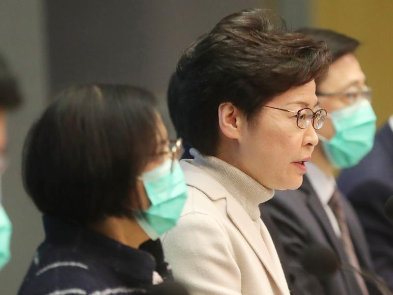 Hong Kong Chief Executive Carrie Lam, center, speaks during a press conference held in Hong Kong, Monday, Feb 3, 2020. Lam says the city will shut almost all land and sea border control points to the mainland from midnight to stem the spread of the novel coronavirus from China. (AP Photo/Achmad Ibrahim)