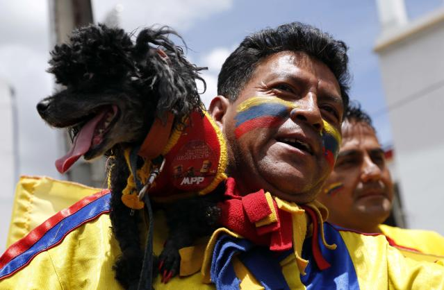 A man with a dog wearing the colors of the Ecuadorean national flag arrives for the 2014 World Cup qualifying soccer match between Ecuador and Uruguay in Quito, Ecuador, Friday, Oct. 11, 2013. (AP Photo/Dolores Ochoa)