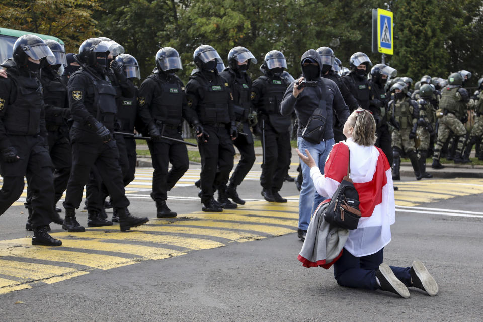 FILE - In this Sunday, Sept. 13, 2020 file photo, a woman covered by an old Belarusian national flag kneels in front of a riot police line as they block Belarusian opposition supporters rally protesting the official presidential election results in Minsk, Belarus. Belarus President Alexander Lukashenko has relied on massive arrests and intimidation tactics to hold on to power despite nearly three months of protests sparked by his re-election to a sixth term, but continuing protests have cast an unprecedented challenge to his 26-year rule. (TUT.by via AP, File)