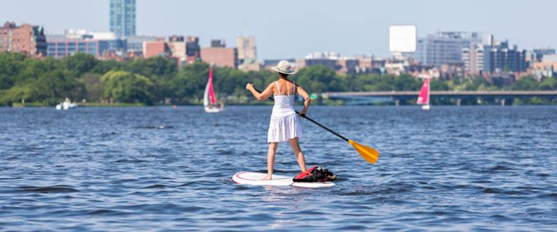 Old woman sailing on the Charles river on sunny day with happy on Boston city background.