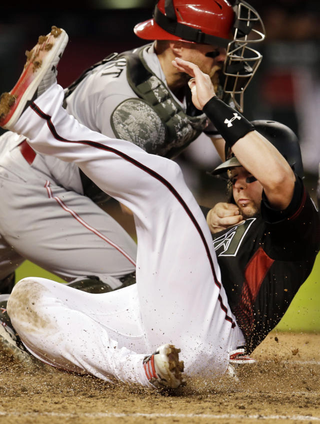 Arizona Diamondbacks' Chris Owings, right, scores a run under the tag by Cincinnati Reds catcher Tucker Barnhart on a ball hit by Nick Ahmed in the fourth inning during a baseball game, Monday, May 28, 2018, in Phoenix. (AP Photo/Rick Scuteri)