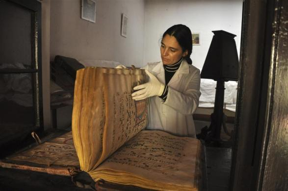 Director of Descalzos Foundation Alberta Alvarez reviews a choral book at a storage room at the Franciscan convent Los Descalzos in Lima, May 24, 2012.