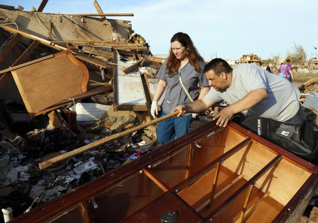 Greg Satterlee (R) shows his wife Genni where he thinks a file cabinet containing important papers may be in their tornado-destroyed home in Moore, Oklahoma May 21, 2013. Rescuers went building to building in search of victims and thousands of survivors were homeless on Tuesday after a massive tornado tore through the Oklahoma City suburb of Moore, wiping out whole blocks of homes and killing at least 24 people. REUTERS/Rick Wilking (UNITED STATES - Tags: DISASTER ENVIRONMENT) - RTXZVR4