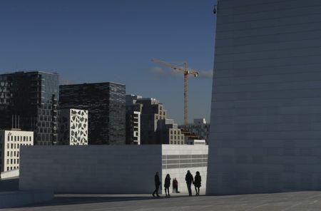 A construction crane is seen operating over Oslo's city skyline from the roof of the Oslo Opera House