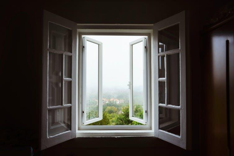 Open windows looking onto the foggy countryside.